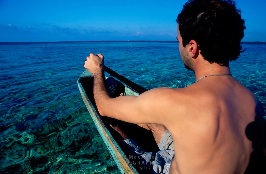 Point of view shot of male traveler paddling a dugout canoe, Tobacco Caye, Belize