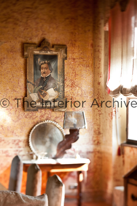 A portrait of the Italian composer Rossini hanging in the dining room