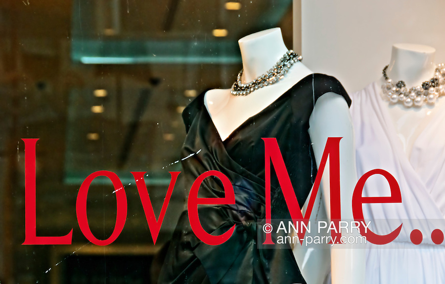 """Tommy Hilfiger Fifth Avenue store, """"Love Me .."""" message written in big red letters, white black dress and white dress with chokers on mannequins, on February 28, 2010, at 681 Fifth Avenue, midtown Manhattan, NYC, New York, USA."""