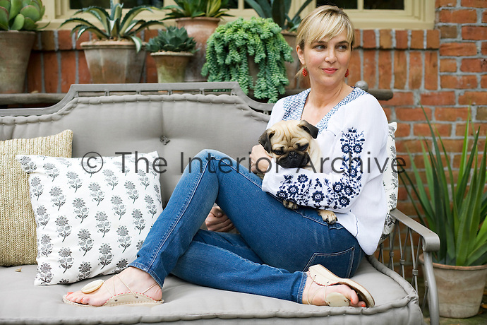 Jill Brinson sits with her pug on a grey-painted sofa in the garden of her Atlanta home