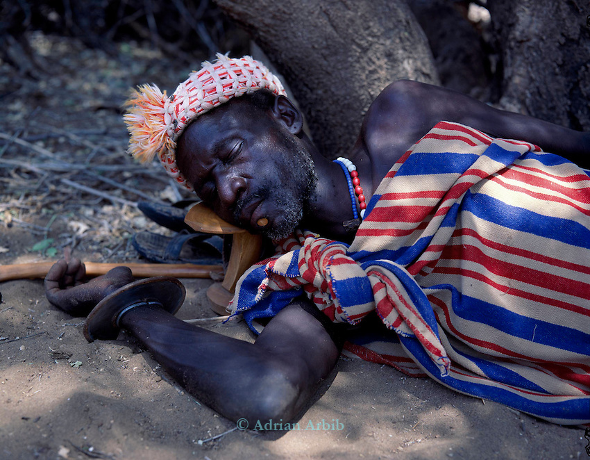 Turkana man sleeping on his head / footstool, Northern Kenya