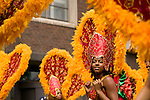 A young woman dressed in red and orange during the street parade for the ZomerCarnaval (Summer Carnival) in Rotterdam, the Netherlands. The street parade is the colorful high point of the Rotterdam carnival. It is a tropical themed parade with over 2000 participants and travels 6km through the center of Rotterdam.