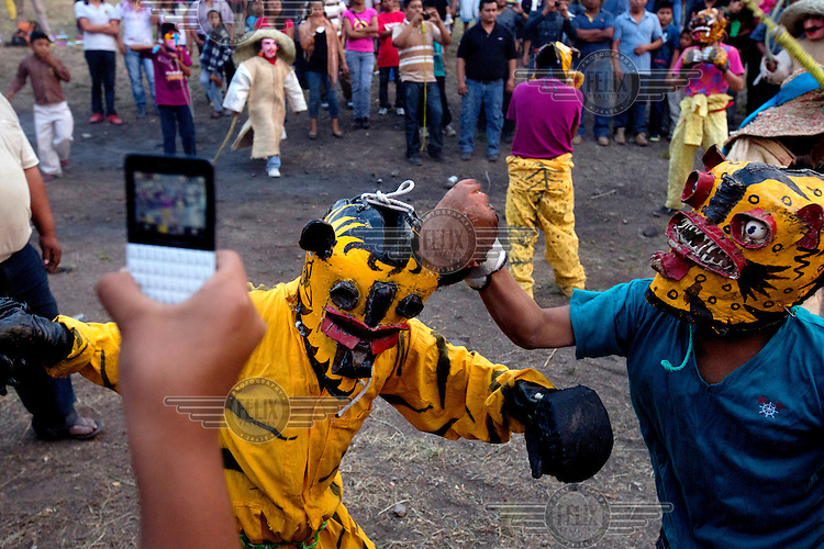 A crowd watches, a take pictures, on as two boys wearing jaguar masks take part in a ritual fight on Cruzco, a mountain that is sacred to people in the region. These events are part of the La Fiestas de la Santa Cruz (Festival of the Holy Cross). This is a petition for rains of pre-Columbian origin and takes place annually in early May. As well as offerings ritual fights take place between people wearing jaguar masks (tecuanis). The ancient traditions state that the blood and sweat, from the fighting, that falls to the ground are an offering to the earth. In return the people ask the gods for rain and therefore, the more tecuanis that fight the more rain will fall.