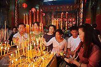 Buddhist worshippers lighting candles,Wat Yai Chaya Mongkol or The Great Temple of Auspicious Victory, Ayutthaya, Thailand