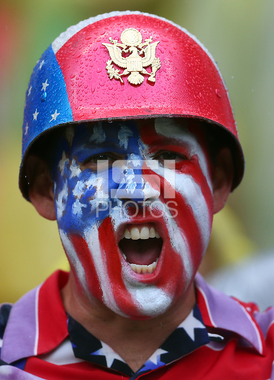 A USA fan with painted face cheers his side on