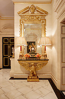 An opulent ante-room with a gilded cornice and a marble floor.  Two lamps stand on a gilded eagle table with an ornate mirror above.