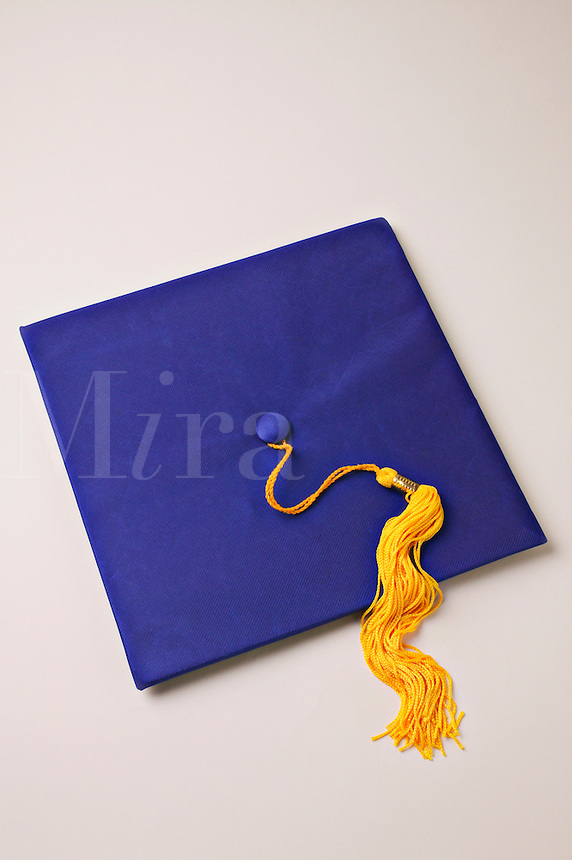 Blue graduation cap with yellow tassel on white background