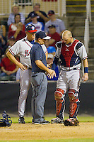 Rome Braves Manager Randy Ingle (12) looks on as trainer Kyle Damschroder examines the right hand of catcher Chase Anselment (37) during the South Atlantic League game  at CMC-Northeast Stadium on August 24, 2013 in Kannapolis, North Carolina.  The Intimidators defeated the Braves 6-1.  (Brian Westerholt/Four Seam Images)