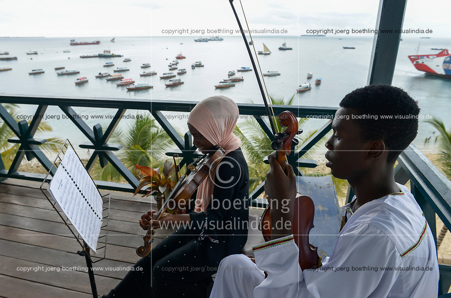 TANZANIA, Zanzibar, Stone town, Dhow countries music academy, girl and boy play violin on balcony with view to the indian ocean and harbour