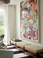 Displayed above a long banquette a large and vibrantly-coloured abstract painting takes up an entire wall of the living room