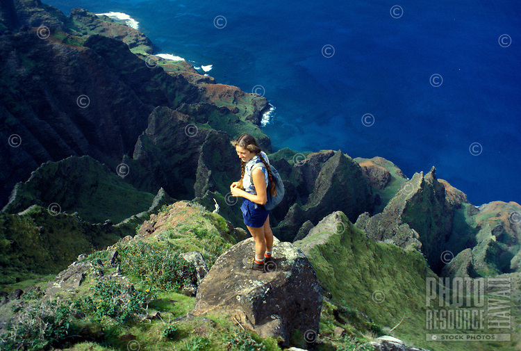 A woman stands on a rocky precipice  along the Na Pali cliffs, on Kauai's north shore.