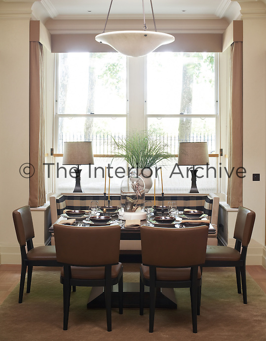 A table is laid for six in this contemporary dining room with a banquette in the bay window