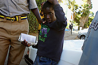 "Street child being apprehended by a police officer. Under the government initative Murambatsvina (Operation Restore Order), many homes and places of work in slum areas were destroyed. Since then there has been a marked increase in the number of children living on the streets of Harare. Murambatsvina, also translated as ""clean up the filth"", continues. Street children are picked up by police and dumped miles out of town to discourage them from being on the street."