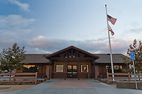 A full width head-on view of the front of the community and park staff building at Stanton Central Park at midnight.  Two tile photographs illustrate the front wall, along with two benches, a mock split rail fence, a flag post, and different colored concrete.  A cloudy sky is above the building, with the remnants of the sunset reflected in the windows.