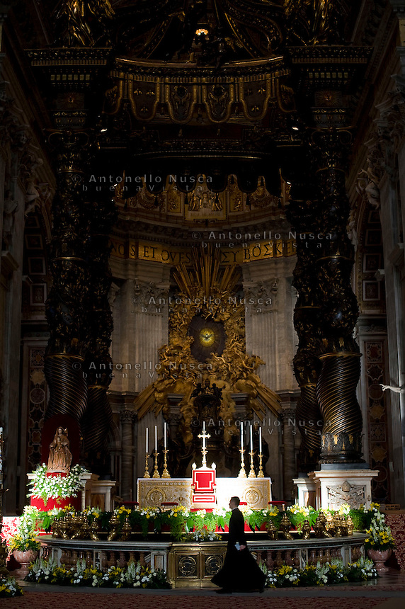 Un prete cammina davanti l'altare della Basilica di San Pietro prima della celebrazione di una messa.