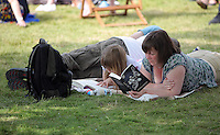 Pictured: A woman and a girl are reading books on the festival green Monday 30 May 2016<br />