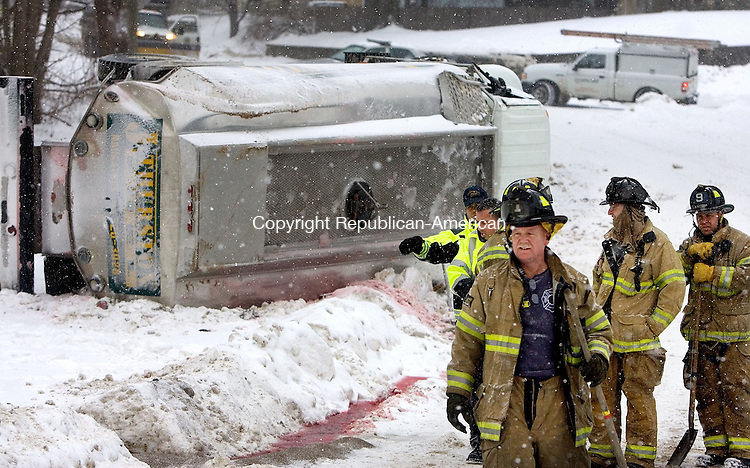 WATERBURY CT. 17 December 2013-121713SV06-Firefighters and Hazmat crews work to contain home heating oil from spilling after a truck rolled over on Hamilton Avenue near Prospect Road in Waterbury Tuesday.<br /> Steven Valenti Republican-American