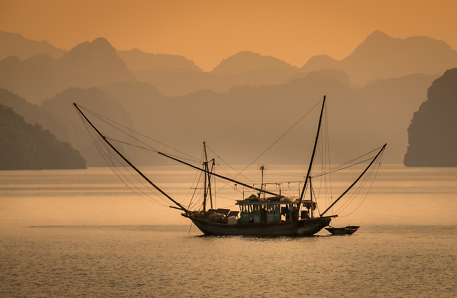 HA LONG BAY, VIETNAM - CIRCA SEPTEMBER 2014:  Fishing boat in Halong Bay, Vietnam at sunset.