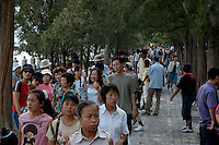 Crowds of tourists walking through a park while on a visit to the Summer Palace, Yiheyuan, China.