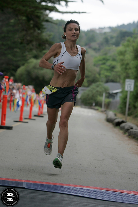 Judy Rabinowitz of Larkspur (10) crosses the finish line at the 99th running of the Dipsea Race at Sintson Beach State Park on Sunday June 14th, 2009.