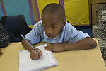Oakland CA  2nd grade African American boy working on writing project in class