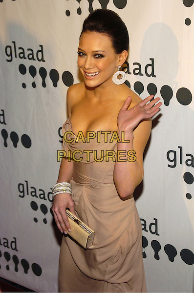 HILARY DUFF.Attending the GLAAD Media Awards (Gay and Lesbian Alliance Against Defamation) New York at the Mariott Marquis Hotel, New York City, NY, USA.March 26th, 2007.half length strapless low cut dress cleavage beige grey gray bracelets clutch bag earrings discs hand palm waving.CAP/ADM/BL.©Bill Lyons/AdMedia/Capital Pictures *** Local Caption ***
