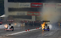 Sep 28, 2013; Madison, IL, USA; NHRA top fuel dragster driver Pat Dakin (right) explodes an engine alongside Steve Torrence during qualifying for the Midwest Nationals at Gateway Motorsports Park. Mandatory Credit: Mark J. Rebilas-