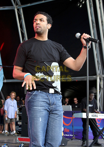 CRAIG DAVID.Performs live in concert at 96.4 BRMB's Party In The Park, Cannon Hill Park, Birmingham, .July 3rd 2005..half length funny gig jeans hand black t-shirt white blue rubber bracelets.Ref: JEZ.www.capitalpictures.com.sales@capitalpictures.com.©Jez Self/Capital Pictures