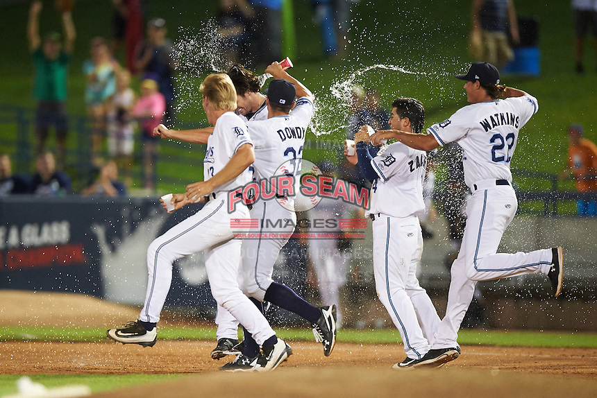 West Michigan Whitecaps first baseman Will Allen (16) is doused with water by teammates Cam Gibson (left), Kyle Dowdy (32), Jose Zambrano (4), and Spenser Watkins (22) after a game winning base hit during a game against the Burlington Bees on July 25, 2016 at Fifth Third Ballpark in Grand Rapids, Michigan.  West Michigan defeated Burlington 4-3.  (Mike Janes/Four Seam Images)