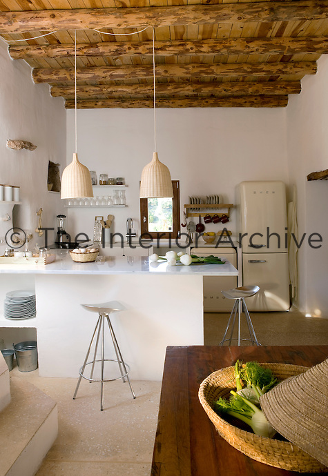 The work surface in the kitchen is made from cool white marble, the floor is of local stone and simple cane pendant lights are suspended from the beamed ceiling