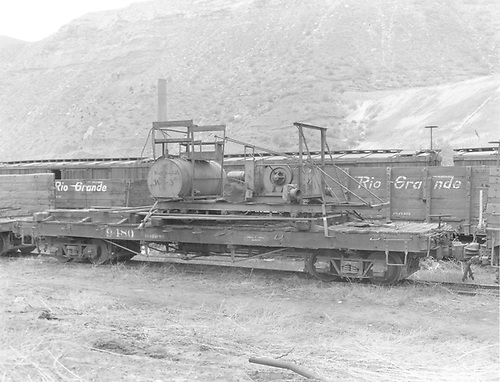 Side view of D&amp;RGW flatcar #9480 rigged with what may be a weedburner rig at Durango.  &quot;W-8-3&quot; is stencilled on the end of the drum that is part of the assembly.<br /> D&amp;RGW  Durango, CO  Taken by Payne, Andy M. - 5/19/1970