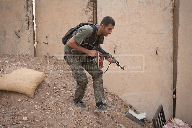 28/09/2014. Rabia, Iraq. A fighter belonging to the Syrian-Kurdish YPG changes position as Islamic State insurgents fire at YPG positions in the Iraqi border town of Rabia.<br /> <br /> Facing each other across the Iraq-Syria border, the towns of Al-Yarubiyah, Syria, and Rabia, Iraq, were taken by Islamic State insurgents in August 2014. Since then The town of Al-Yarubiyah and parts of Rabia have been re-taken by fighters from the Syrian Kurdish YPG. At present the situation in the towns is static, but with large exchanges of sniper and heavy machine gun fire as well as mortars and rocket propelled grenades, recently occasional close quarter fighting has taken place as either side tests the defences of the other.