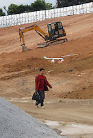 20120116 CHINA GUANGDONG PROVINCE : A man walks past an excavator in Hallstatt, China's copy of the Austrian alpine town of the same name, Boluo Township, Huizhou City, Guangdong Province, China, 16 January 2012. Property developments such as this are expected to run into financial difficulites in 2012 as the Chinese economy and property market continue to cool, in reaction to the ongoing sovereign debt crisis in Europe.<br /> SINOPIX / ALEX HOFFORD