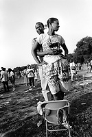 USA. New York. Central Park. A loving afro-american couple stands up on a plastic chair. 20.05.86 © 1986 Didier Ruef