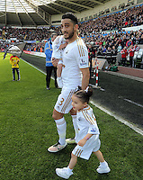 Neil Taylor with his two children walks to the pitch before the Barclays Premier League match between Swansea City and Chelsea at the Liberty Stadium, Swansea on April 9th 2016