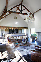 The open plan living area of the house is situated in a massive barn with a fireplace the size of a forge