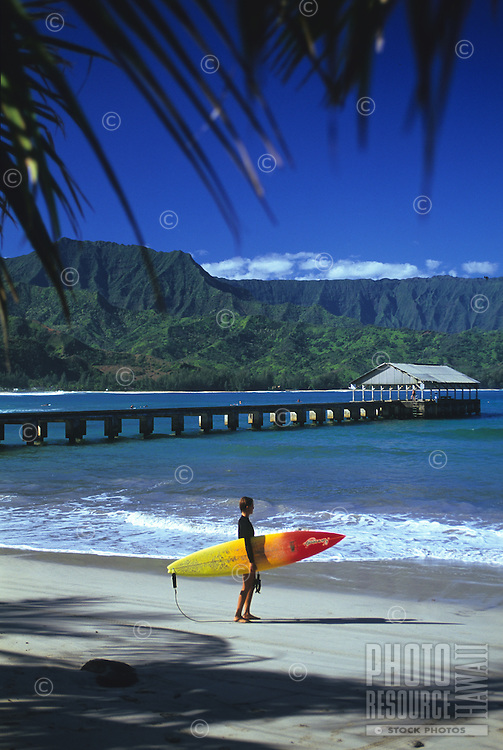 A surfer checks out the waves at Hanalei Bay on the north shore of Kaua'i.