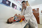 Dr. Mohi El Sharqawi examines a child in the pediatric department of the Al Ahli Arab Hospital in Gaza City. The Anglican Church-affiliated hospital is a member of the ACT Alliance.<br /> <br /> The 2014 war provoked serious damage to Gaza's health infrastructure. Seventeen hospitals, 56 primary health care facilities and 45 ambulances were damaged or destroyed. Sixteen health care workers were killed and 83, most of them ambulance drivers and volunteers, were injured. <br /> <br /> Parental consent obtained.