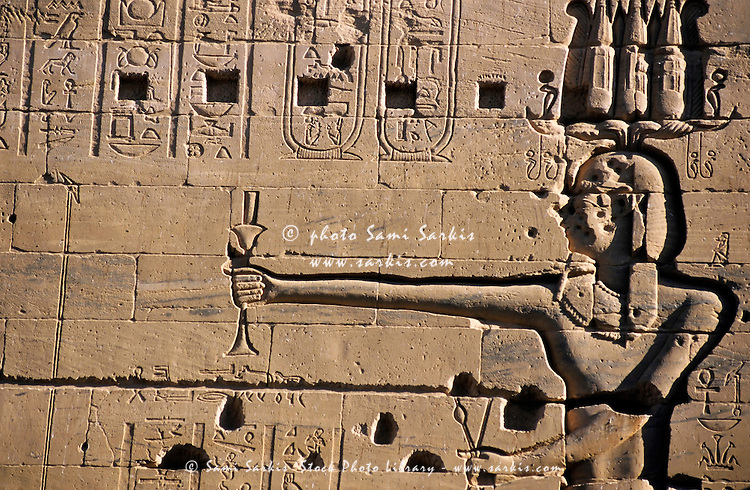 Detail of a carved stone wall at the ancient temple for Isis on the island of Philae on the Nile river, Egypt.