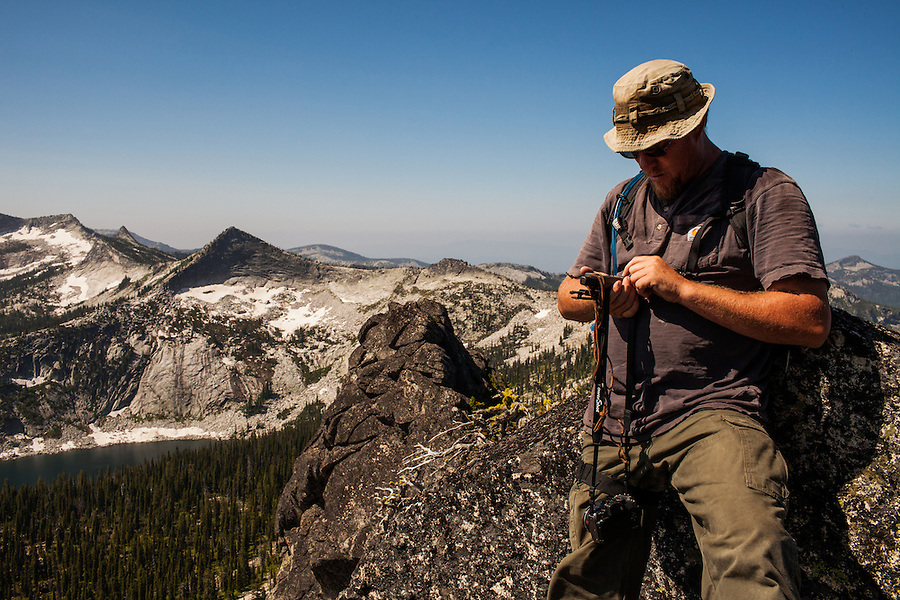 A male adult hiker checks his GPS position a few feet from the top of Harrison Peak in Northern Idaho's Selkirk Range.