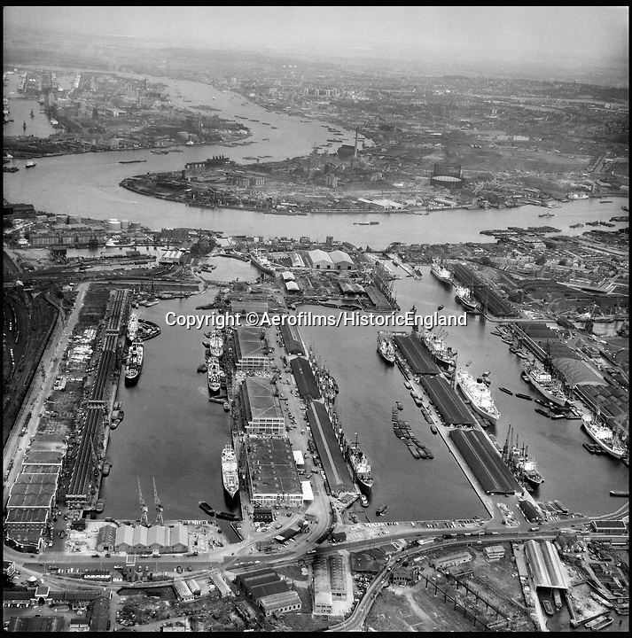 BNPS.co.uk (01202 558833)<br /> Pic: Aerofilms/HistoricEngland/BNPS<br /> <br /> West India Docks, London, 9 June 1964 - now Canary Wharf.<br /> <br /> Stunning historic aerial photos of seaside towns, naval bases, ports and shipyards which tell the story of Britain's once-great maritime tradition feature in a new book.<br /> <br /> The fascinating archive of black and white images includes views from a bygone age such as Brighton's famous West Pier, Grimsby's burgeoning fishing fleet, and London's dock yards.<br /> <br /> Iconic ships were also captured from the skies including the Cutty Sark in its final seaworthy years on the Thames, HMY Britannia in 1959, the RMS Queen Mary in 1946 and the SS Queen Elizabeth in 1969 about to make her maiden voyage.<br /> <br /> England's Maritime Heritage from the Air, by Peter Waller, is published by English Heritage and costs £35.