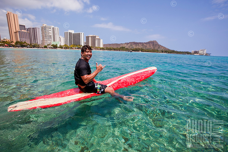Local man enjoying a surf session on a sunny day in Waikiki