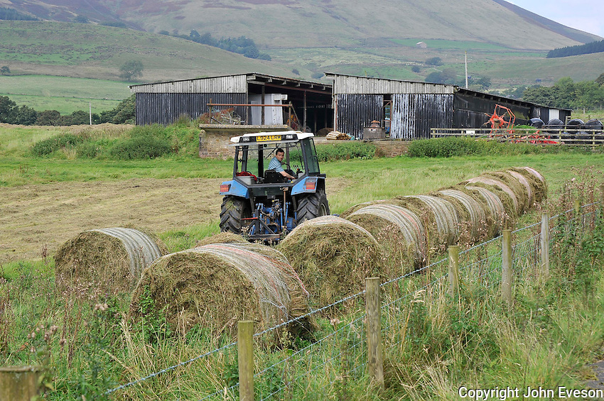 Stacking big bales of silage ready for wrapping, Whitewell, Lancashire....Copyright..John Eveson, Dinkling Green Farm, Whitewell, Clitheroe, Lancashire. BB7 3BN.01995 61280. 07973 482705.j.r.eveson@btinternet.com.www.johneveson.com