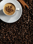 Cup of coffe latte and cinnamon sticks standing on coffee beans background