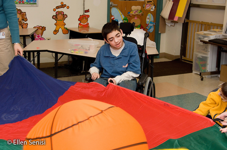 MR / Albany, NY.Langan School at Center for Disability Services .Ungraded private school which serves individuals with multiple disabilities.Child holds parachute during lesson with the objective of helping develop coordination and grasping skills while playing. Boy: 11, cerebral palsy, expressive and receptive language delays .MR: Bro12.© Ellen B. Senisi