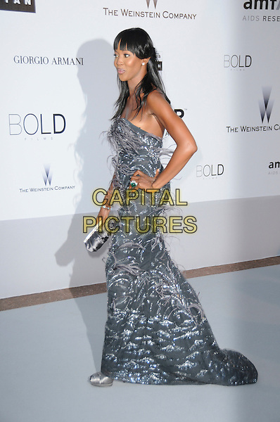 NAOMI CAMPBELL.arrivals at amfAR's Cinema Against AIDS 2010 benefit gala at the Hotel du Cap, Antibes, Cannes, France during the Cannes Film Festival.20th May 2010.amfAR full length long maxi dress silver feathers hand on hip side strapless  grey gray clutch bag .CAP/CAS.©Bob Cass/Capital Pictures.