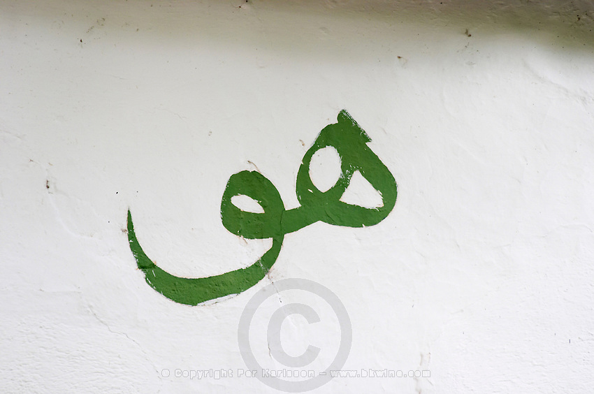 a sign painted on the white wall meaning Him (God) in Arab writing (spelled 'hu' as used by a certain religious sect.). The source of the Buna river and the house of the Whirling Dervishes, an old Muslim monastery, Blagaj. Federation Bosne i Hercegovine. Bosnia Herzegovina, Europe.