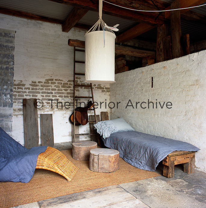 A wicker chair, a heavy wooden bench seat used as a bed and sawn off tree trunks as tables is the basic furniture in a  room, which has a rustic, unfinished look with painted brick walls and bare floorboards