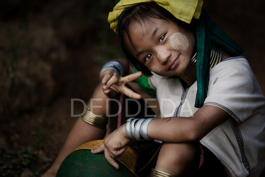 "A young female member of the ""long neck"" Karen Tribe from Burma gives the ""peace"" sign. The Karen Tribe are Burmese refugees. This young girl was at her refugee camp near the Burmese (Myanmar) border near Mae Hong Son in northern Thailand."