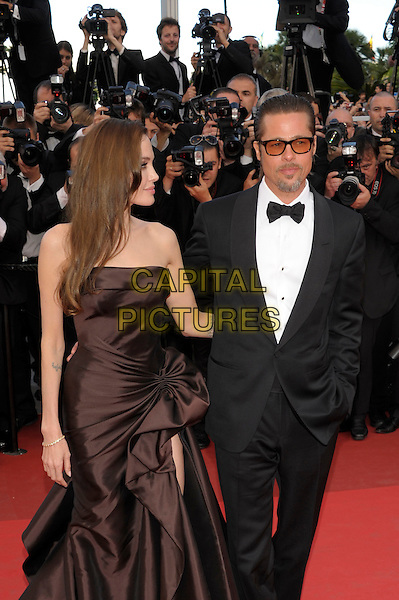 ANGELINA JOLIE & BRAD PITT.'The Tree of Life' premiere at the Palais des Festival, 64th International Cannes Film Festival, France.16th May 2011.half 3/4 length strapless silk satin brown dress gown black tux tuxedo tinted glasses sunglasses shades couple gathered goatee facial hair photographers press profile.CAP/PL.©Phil Loftus/Capital Pictures.